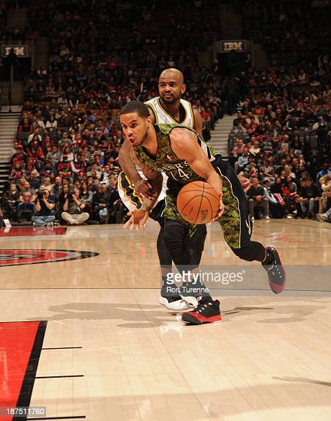 DJ Augustin of the Toronto Raptors drives to the basket against Jamaal Tinsley of the Utah Jazz on November 9 2013 at the Air Canada Centre in...