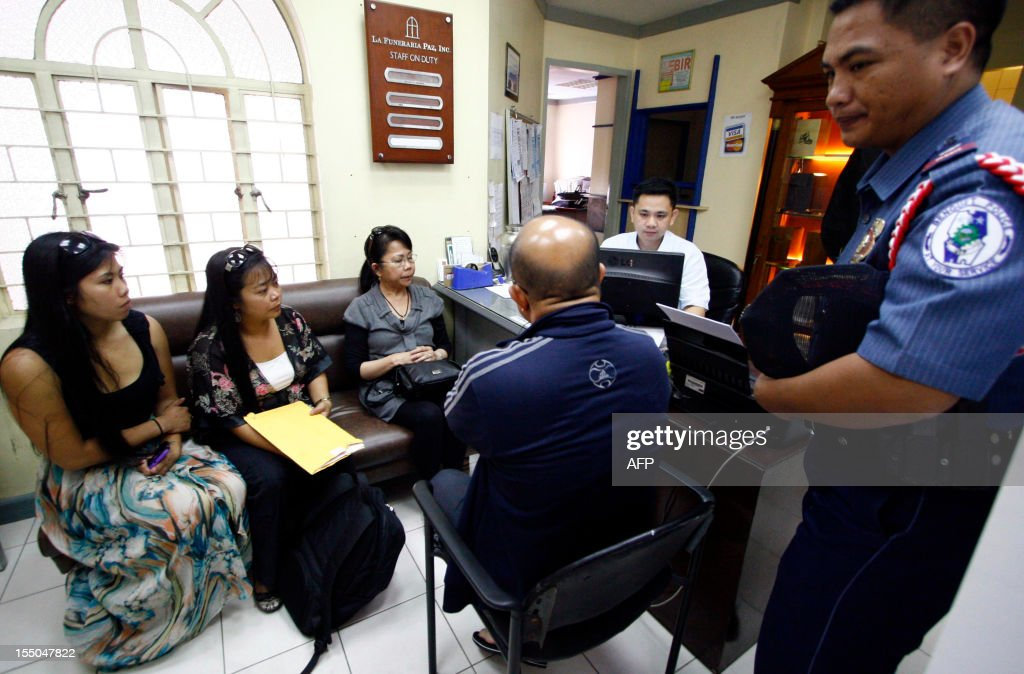 Augustina Adams (back, R), wife of murdered Australian yatch designer Joseph Adams accompanied by her daughters Irene (back, C) and Lailani (back L) talks to funeral parlor worker in Baguio City, Benguet province, north of Manila on October 31, 2012, as they claim the body of her late husband. Adams, 81, who was known for designing swift yachts including the Helsal, which took line of honours at the record-breaking 1973 Sydney to Hobart race, was found murdered at his mountain home in the Philippines on October 15, 2012. AFP PHOTO / JJ Landingin