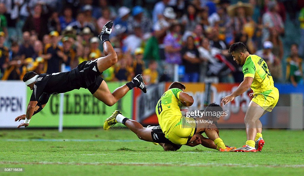Augustine Pulu of New Zealand flys over the top of Greg Jeloudev of Australia as he is tackled by Rieko Ioane of New Zealand during the 20146 Sydney Sevens match between Australia and New Zealand at Allianz Stadium on February 6, 2016 in Sydney, Australia.