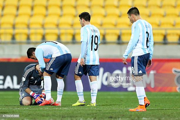 Augusto Batalla of Argentina is consoled by teammate Cristian Pavon while Emiliano Buendia and Leonardo Rolon look on during the FIFA U20 World Cup...