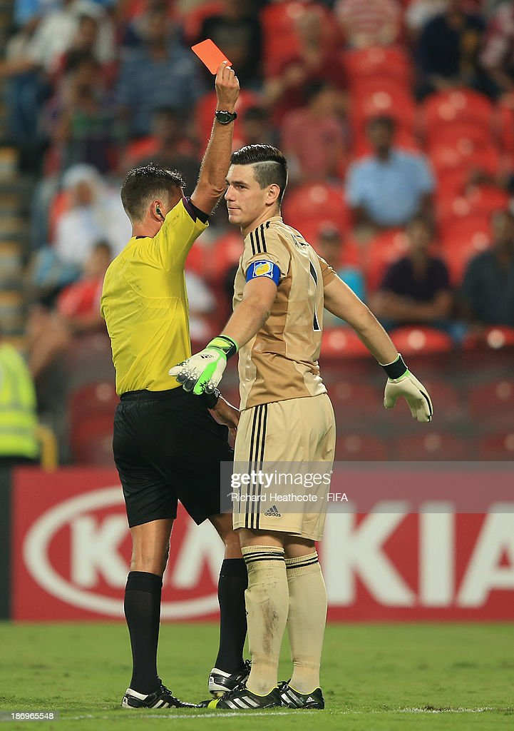 Augusto Batalla of Argentina is sent off by referee Gianluca Rocchi of Italy during the FIFA U-17 World Cup UAE 2013 Semi Final match between Argentina and Mexico at the Mohamed Bin Zayed Stadium on November 5, 2013 in Abu Dhabi, United Arab Emirates.