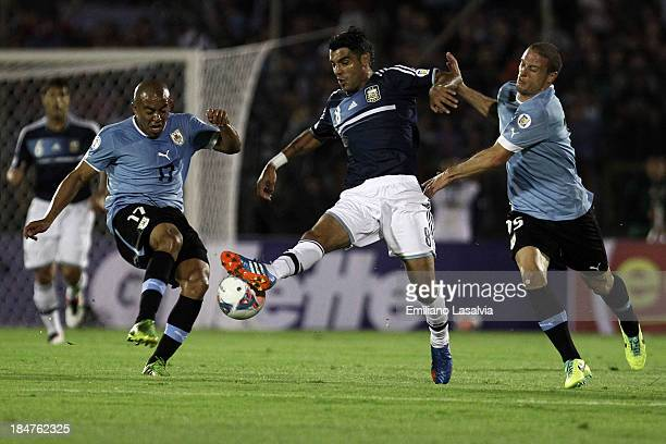 Augusto Fernandez of Argentina fights for the ball with Diego Perez and Egidio Rios of Uruguay during a match between Uruguay and Argentina as part...