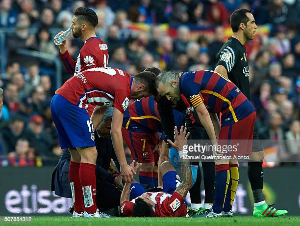 Augusto Fernandez of Atletico de Madrid lies injured on the pitch during the La Liga match between FC Barcelona and Atletico de Madrid at Camp Nou on...