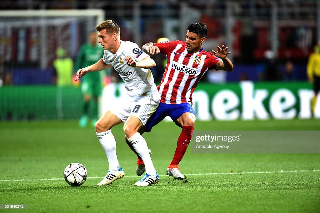 Augusto Fernandez (R) of Atletico Madrid and Toni Kroos (L) of Real Madrid vie for the ball during the UEFA Champions League Final between Real Madrid CF and Atletico Madrid at the Giuseppe Meazza Stadium in Milan, Italy on May 28, 2016 in Milan, Italy.
