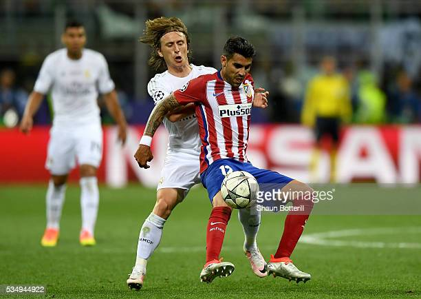 Augusto Fernandez of Atletico Madrid battles for the ball with Luka Modric of Real Madrid during the UEFA Champions League Final match between Real...