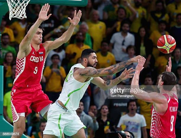 Augusto Lima of Brazil passes the ball against Dario Saric of Croatia and Mario Hezonja of Croatia during the Men's Basketball Preliminary Round...