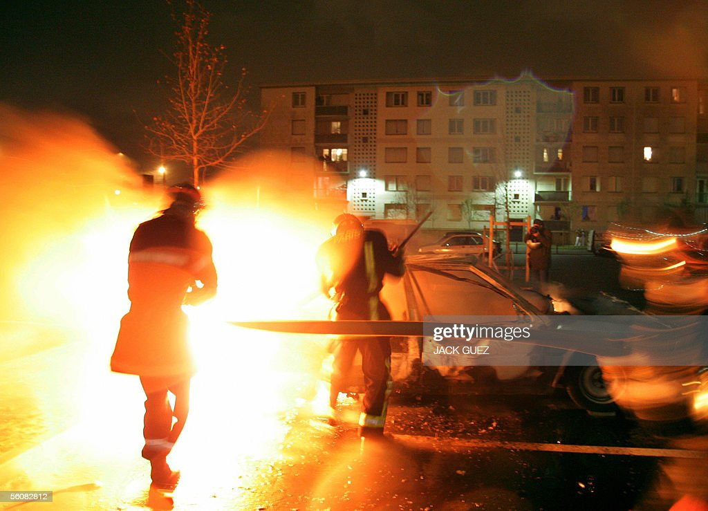 Firefighters spray water on a car near a warehouse set ablaze in the early hours of 04 November 2005 in AulnaysousBois on the eighth consecutive...