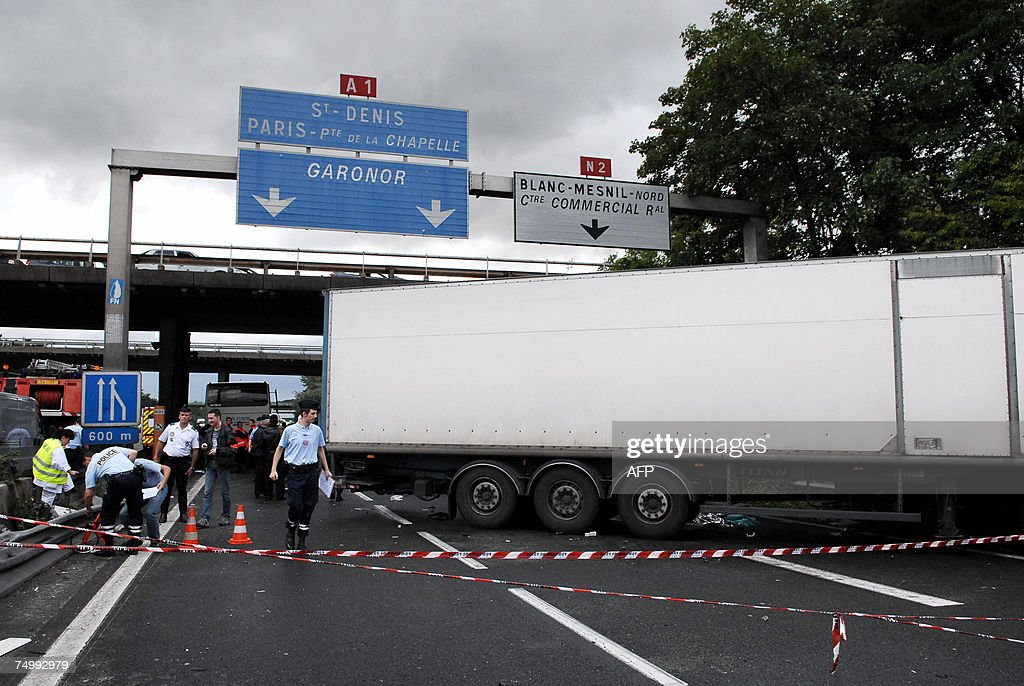 Police officers stand near the wreckage of a truck that collided with a coach of Air France airline company on a road near AulnaysousBois...