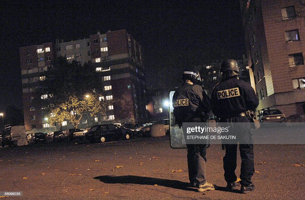 Policemen stand guard next to a burning car 05 November 2005 in the Cite de l'Europe neighborhood in AulnaysousBois a northern surburb of Paris on...