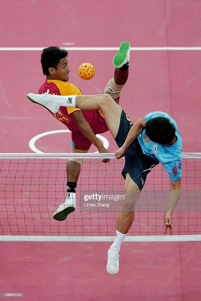 Aung Pyae Tun of Myanmar and Kim Youngman of South Korea challenge for the ball in the Sepaktakraw Men's Regu Semifinal during day thirteen of the 2014 Asian Games at Bucheon Gymnasium on October 2, 2014 in Incheon, South Korea.