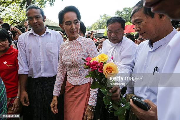 Aung San Suu Kyi Myanmar's opposition leader and chairperson of the National League for Democracy center left arrives at the party headquarters in...