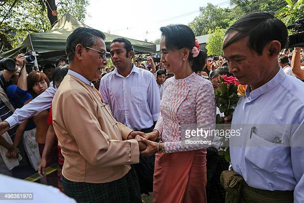 Aung San Suu Kyi Myanmar's opposition leader and chairperson of the National League for Democracy center right greets Tin Oo cofounder of the NLD as...