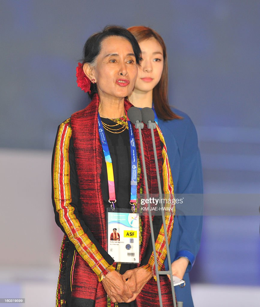 Aung San Suu Kyi (L), Myanmar's opposition leader, delivers a speech as Olympic figure skating gold medalist Kim Yuna (R) watches at the opening of the Special Olympics World Winter Games in Pyeongchang, about 180 km (112 miles), east of Seoul on January 29, 2013. The democracy leader and Nobel peace laureate was a guest of honour at the opening of the Special Winter Olympics in the northeastern mountain resort of Pyeongchang -- site of the full 2018 Winter Games.
