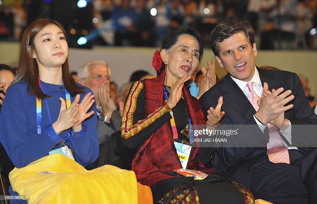 Aung San Suu Kyi(C), Myanmar's opposition leader, flanked by Olympic figure skating gold medalist Kim Yuna (L) and Timothy Perry Shriver (R), chairman and CEO of the Special Olympics, applauds at the opening of the Special Olympics World Winter Games in Pyeongchang, about 180 km (112 miles), east of Seoul on January 29, 2013. The democracy leader and Nobel peace laureate was a guest of honour at the opening of the Special Winter Olympics in the northeastern mountain resort of Pyeongchang -- site of the full 2018 Winter Games. AFP PHOTO / KIM JAE-HWAN / POOL