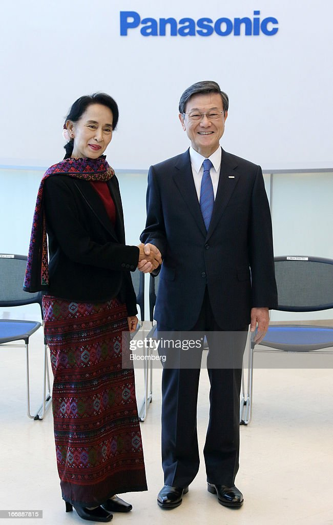 Aung San Suu Kyi, Myanmar's opposition leader, left, shakes hands with Fumio Otsubo, chairman of Panasonic Corp., at Panasonic Center Tokyo in Tokyo, Japan, on Thursday, April 18, 2013. Suu Kyi said on April 17 foreign investment in the newly democratizing nation is being held up by inadequate infrastructure and uncertainty over investment laws. Photographer: Tomohiro Ohumi/Bloomberg via Getty Images