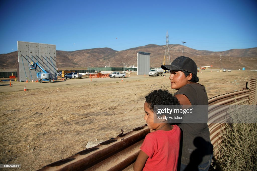Aurelia Lopez and her daughter Antonia overlook construction of border wall prototypes on October 5, 2017 in Tijuana, Mexico. Prototypes of the border wall propopsed by President Donald Trump are being built just north of the U.S.- Mexico border, where competitors who are hoping to gain approval to build the wall have until the first of next month to complete their work.