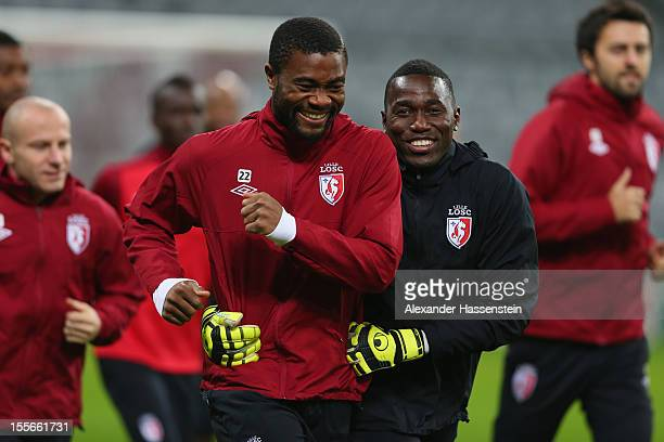 Aurelien Chedjou smiles with his team mate Barel Mouko during a OSC Lille training session ahead of their UEFA Champions League group F match against...