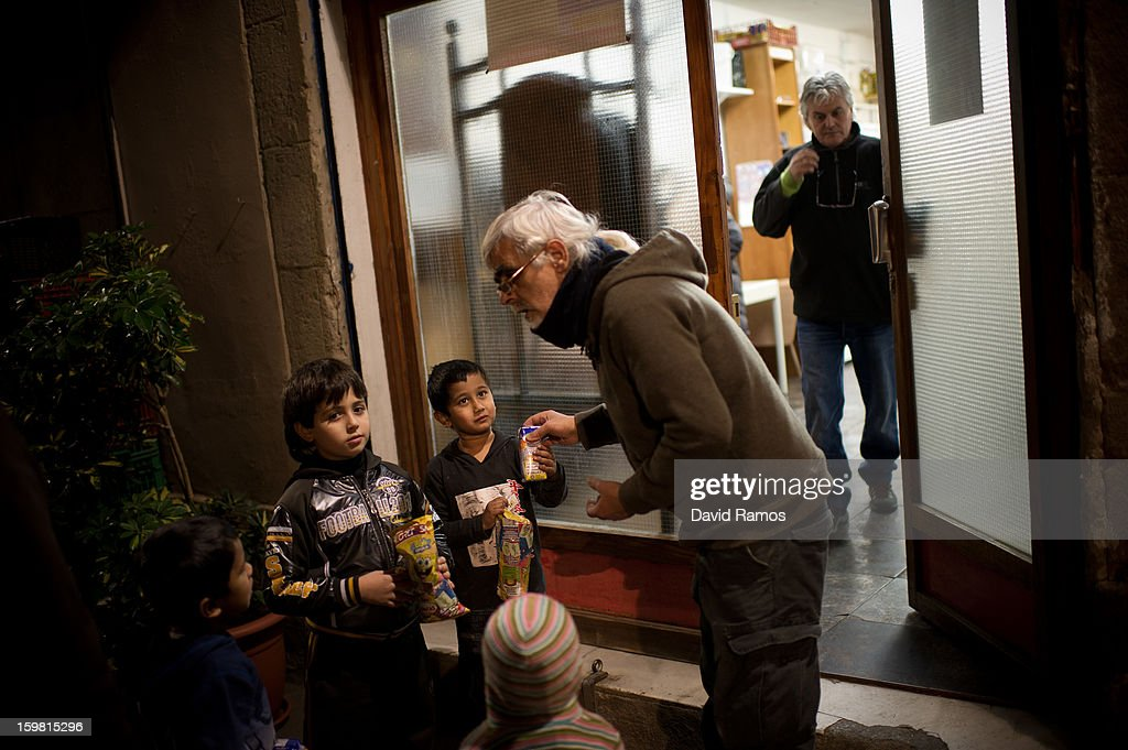 Aurelio from Spain, 51, gives out sweets among children at the entrance of the 'El Chiringuito de Dios' ('The Stall of God') at the end of the day after serving meals for almost 200 needy people and to hand food out to 20 families on January 4, 2013 in Barcelona, Spain. The German pastor Wolfgang Striebinger has lived in Barcelona since 1991, originally employed to minister to youths during the Barcelona Olympic Games, he decided to stay and since 2000 has run 'El Chinguito de Dios' (The Stall of God). In his mission to support the homeless, Wolfgang and his volunteers offer a place for up to 200 people to come and have some food daily and also offering them assistance with grooming and clothes. Many of the volunteers are homeless and help out in return for meals and a bed. Wolfgang's ethos is to provide peace, calm and dignity to all those that need it amongst Barcelona's burgeoning homeless population. Due to the economic situation his doors are now also open to the long term unemployed and families with little or no income. According to the latest figures 21.8% of the Spanish populations are living below the poverty line.
