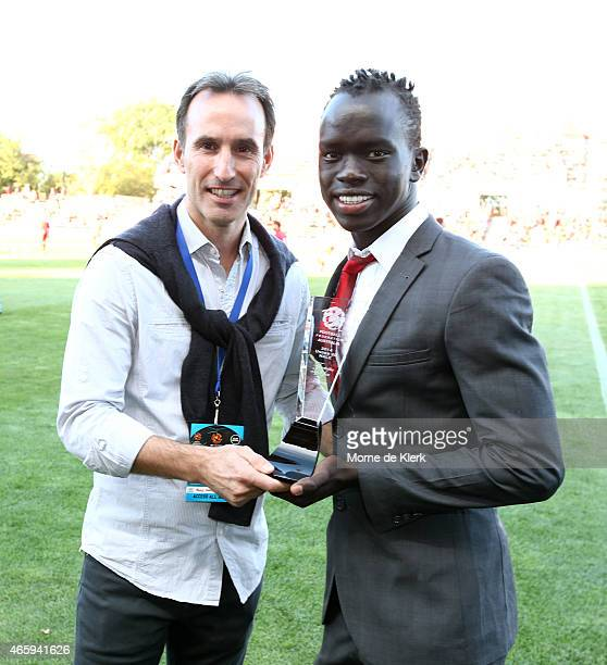 Aurelio Vidmar presents Awer Mabil of Adelaide United with a trophy that was awarded to him for being the Football Federation Australia under 20 male...