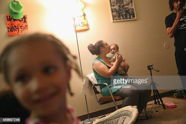 Aurellia Davis hangs out with her family while preparing Thanksgiving dinner at her home in the Canfield Green Apartments where Michael Brown was...