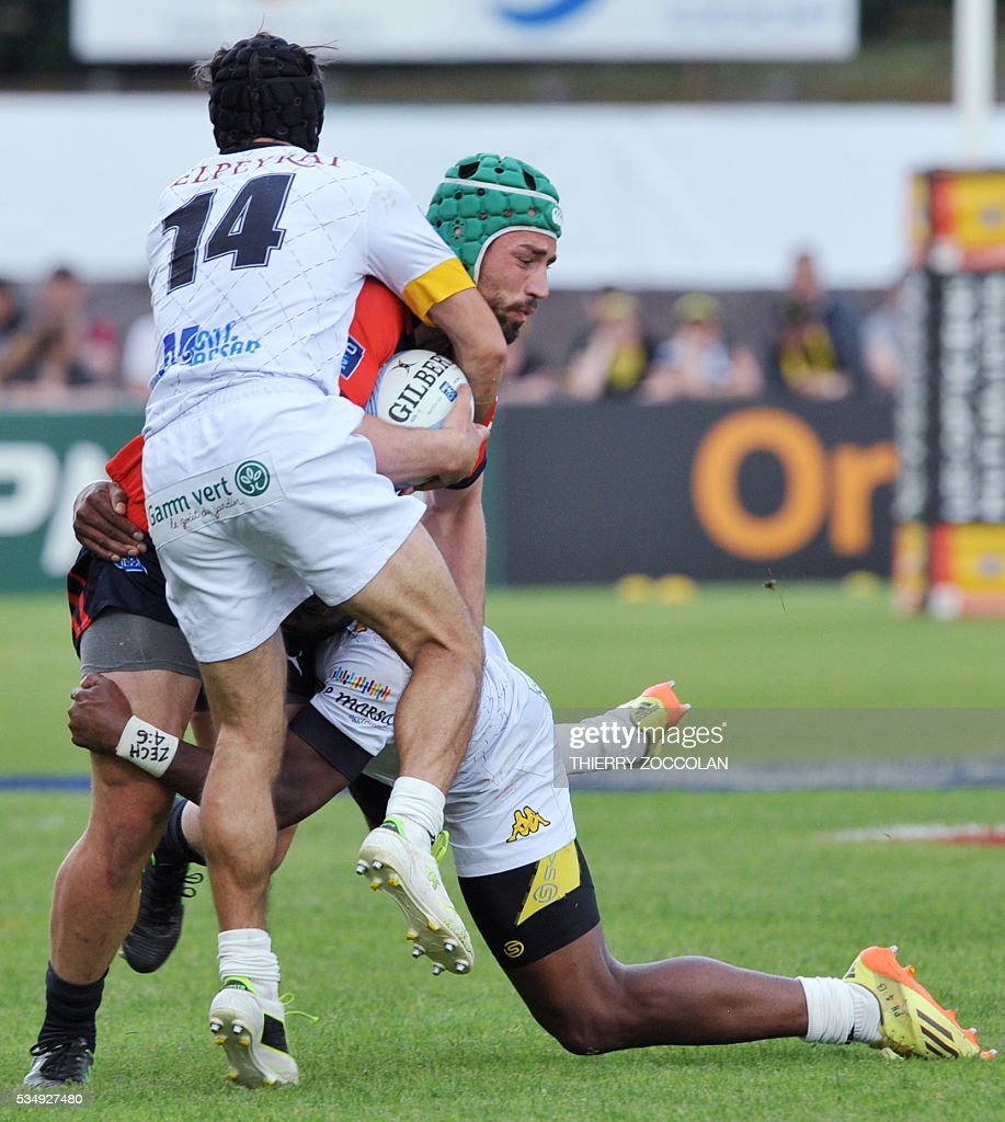 Aurillac's Georgian winger Merab Sharikaze(R) is tackled during the French Union Pro D2 rugby match Aurillac vs Mont-de-Marsan at the Jean Alric stadium in Aurillac, central France, on May 28, 2016.