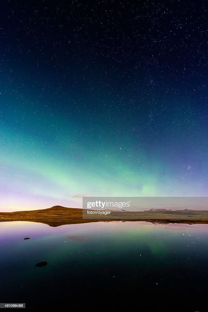 Aurora and glittering stars reflecting in tranquil mountain lake Iceland : Stock Photo
