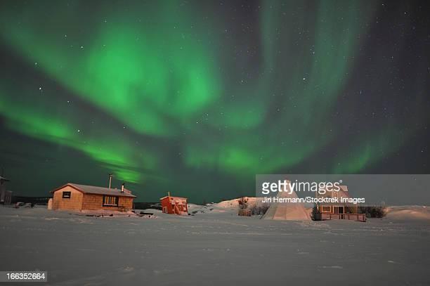 Aurora borealis above village on shoreline of Great Slave Lake, Yellowknife, Northwest Territories, Canada.