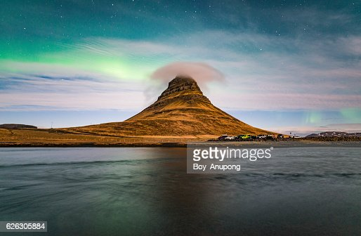 Aurora borealis and cloud cap over the Kirkjufell mountain the iconic landmark of west Iceland.