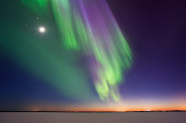 Vivid display of Northern Lights and Moon above frozen lake after sunset.