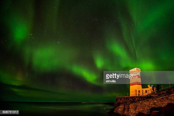 Aurora Borealis in a Winter sky over a lighthouse in Iceland