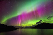 Aurora Borealis, also known as the Northern loights, putting a show on dancing over Loch Glascarnoch, by Garve, Highlands of Scotland, UK.
