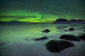 The aurora borealis over Uttakleiv beach on the Lofoten in northern Norway in winter.