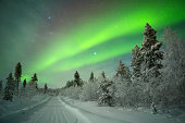 Beautiful northern lights (aurora borealis) over a snowy track in the Arctic.