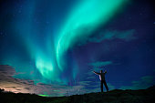 Person standing on hill watching aurora borealis in  iceland Badlands