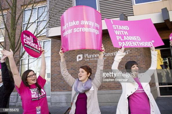 Aurora Jewell Mandi Moshay and Kirsten Dees hold up signs following a press conference by US Sen Patty Murray outside at a Planned Parenthood Clinic...
