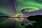 Auroras over Eillidavatn close to Reykjavik in Iceland. calm water reflecting the northern lights blazing in the sky.