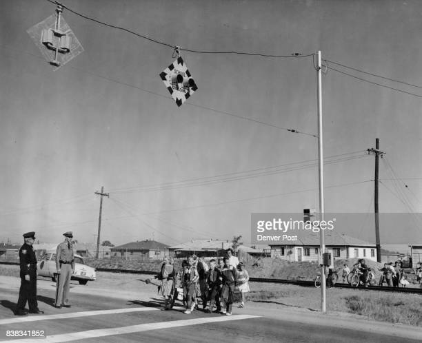 Aurora Patrolman Henry R Hutton and state highway Patrolman D F Hiatt check the operation of a school walk light as Hoffman Heights youngsters cross...