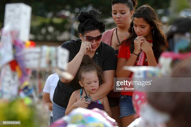 Aurora resident Gina Martinez is breaks down with her daughters clockwise from top–Alezia 16 Lauren 13 and Aaron while visiting the public memorial...