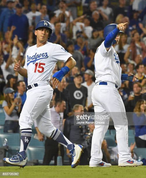 Austin Barnes and Joc Pederson of the Los Angeles Dodgers both score on a single by Corey Seager in the eighth inning of the game against the Chicago...