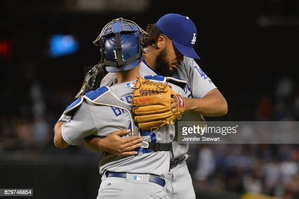Austin Barnes and Kenley Jansen of the Los Angeles Dodgers hug after closing out the MLB game against the Arizona Diamondbacks at Chase Field on...