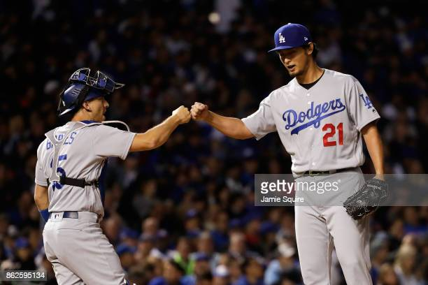 Austin Barnes and Yu Darvish of the Los Angeles Dodgers celebrate before Darvish is relieved in the seventh inning against the Chicago Cubs during...