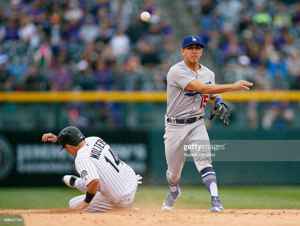 Austin Barnes #15 of the Los Angeles Dodgers attempts to turn a double play as Tony Wolters #14 of the Colorado Rockies slides into second base during the eighth inning at Coors Field on October 1, 2017 in Denver, Colorado.