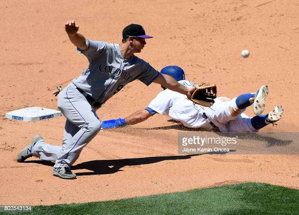 Austin Barnes of the Los Angeles Dodgers beats the throw to DJ LeMahieu of the Colorado Rockies for a stolen base in the game at Dodger Stadium on...