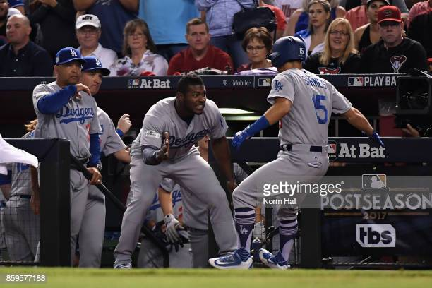 Austin Barnes of the Los Angeles Dodgers high fives Yasiel Puig after hitting a one run home run during the sixth inning of the National League...