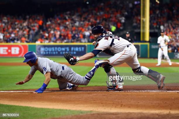 Austin Barnes of the Los Angeles Dodgers is tagged out trying to score by Brian McCann of the Houston Astros during the sixth inning in game four of...