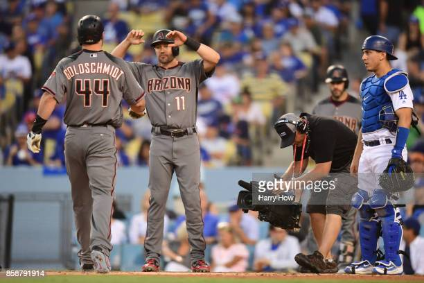 Austin Barnes of the Los Angeles Dodgers looks on as Paul Goldschmidt is congratulated by his teammate AJ Pollock of the Arizona Diamondbacks after...