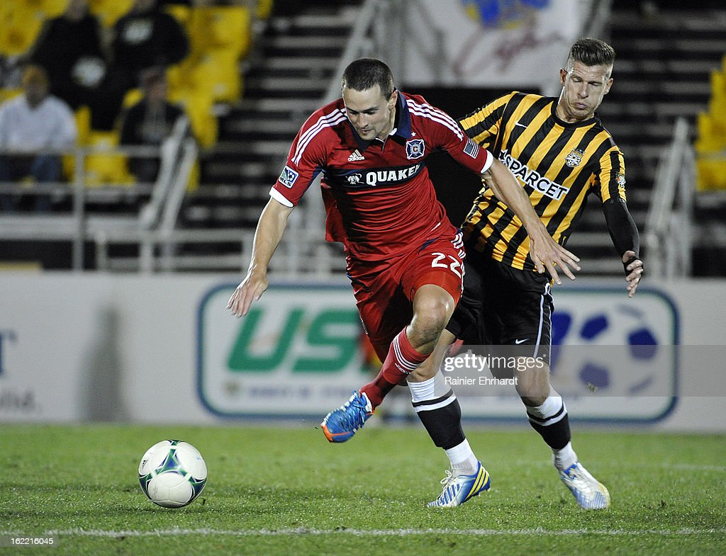 Austin Berry #22 of the Chicago Fire and Nicki Paterson #8 of the Charleston Battery battle for the ball during the first half of a game at Blackbaud Stadium on February 20, 2013 in Charleston, North Carolina.