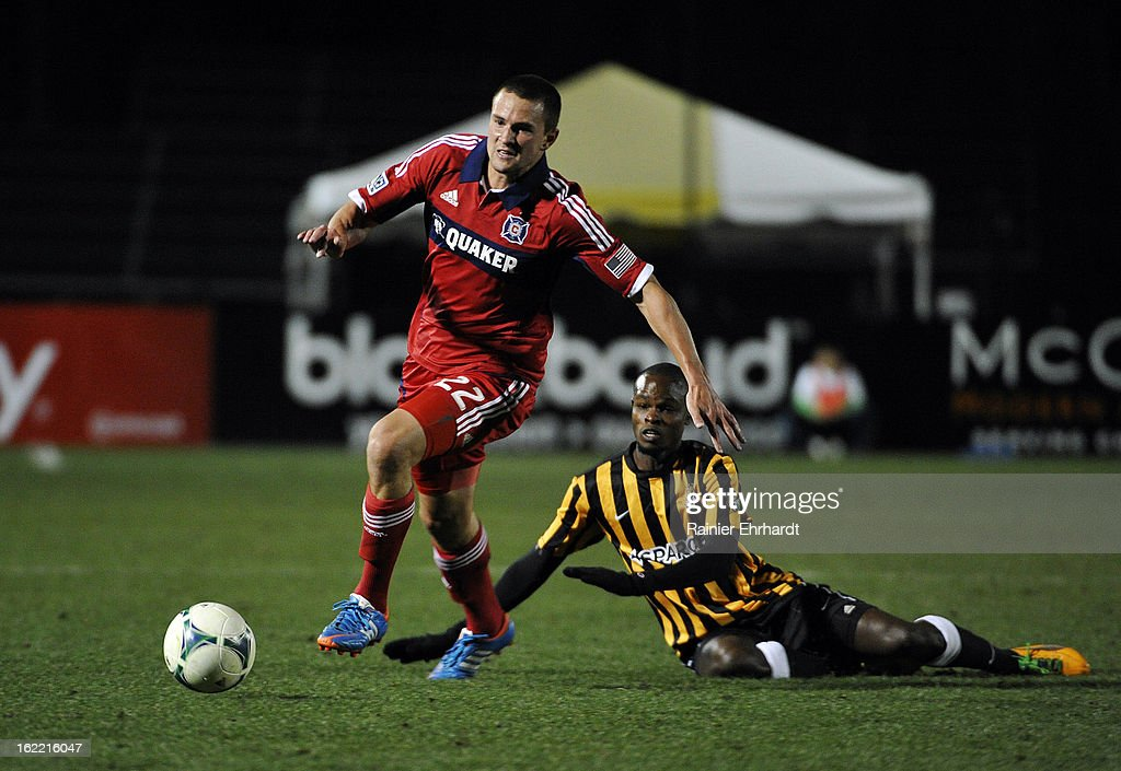 Austin Berry #22 of the Chicago Fire heads down the field as Dane Kelly #9 of the Charleston Battery falls during the first half of a game at Blackbaud Stadium on February 20, 2013 in Charleston, North Carolina.