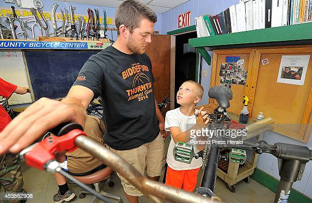 Austin Cantara right looks up to Volunteer and Program Director Andrew Burnell as he gets help replacing the brake pads on his bicycle at the...