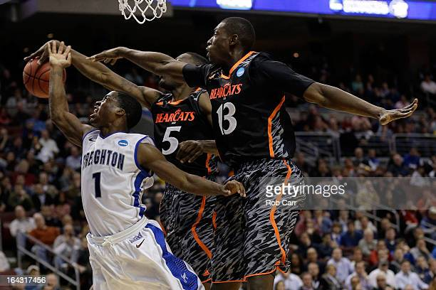 Austin Chatman of the Creighton Bluejays goes up for a shot against Justin Jackson and Cheikh Mbodj of the Cincinnati Bearcats in the second half...